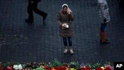 一位乌克兰妇女在基辅街头的抗议者纪念碑前哭泣。 2014年2月23日