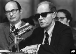 FILE - Convicted Watergate conspiritor E. Howard Hunt, wearing dark glasses, begins his seconds day of testimony before the Senate Watergate Committee in this Sept. 25, 1973 photo in Washington, D.C. Hunt helped organize the Watergate break-in that led to the greatest scandal in American political history and the downfall of Richard Nixon's presidency.