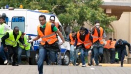 Paramedics run outside the Westgate Mall in Nairobi after heavy shooting, Sept. 23, 2013.
