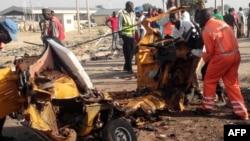 Le personnel de l'agence nationale de gestion des urgences (NEMA) déplace la carcasse d'une voiture près de la frontière somalienne, au Nigeria, le 29 octobre 2016.