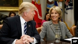 FILE - In this Feb. 14, 2017 file photo, President Donald Trump talks to Education Secretary Betsy DeVos in the Roosevelt Room of the White House in Washington. A new study published Tuesday has found increased support for charter schools and private school voucher programs. The study suggests that Republican Party support for these programs had a strong influence on the increase. (AP Photo/Evan Vucci, File)
