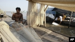 A Cambodian man fixes his fishing nets during the dry season on the Mekong river bank Tuesday, Feb. 28, 2012, in Phnom Penh, Cambodia. (AP Photo/Heng Sinith)