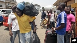 People walk with their belongings towards a railway station as they leave Abidjan, Ivory Coast, March 29, 2010