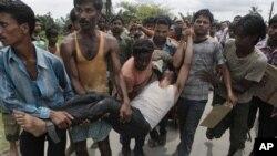 인도 아삼 주에서 일어난 종족 간 충돌 중에 부상자를 옮기는 주민들.