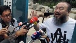 آی وی وی هنرمند و فعال سیاسی چین با خبرنگاران در برابر منزل مسکونی اش در پکن، چین. ۲۳ ژوئن ۲۰۱۱