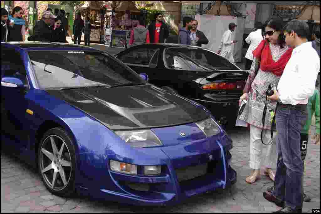 میلے میں شریک شہری ایک گاڑی کا ماڈل دیکھتے ہوئے