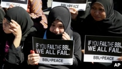 Filipino Muslims display messages during a rally at the Lower House to call for the passage of Bangsamoro Basic Law, or BBL, in Quezon city, northeast of Manila, Tuesday, Feb. 10, 2015.