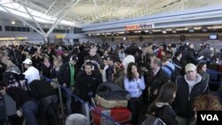 Ratusan penumpang yang terlantar di bandara John F. Kennedy, New York menunggu informasi status penerbangan yang terhambat bencana badai salju.