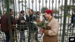 Seorang pria Tunisia hendak meletakkan bunga di pintu masuk Museum Nasional Bardo di Tunis (21/3). (AP/Michel Euler)