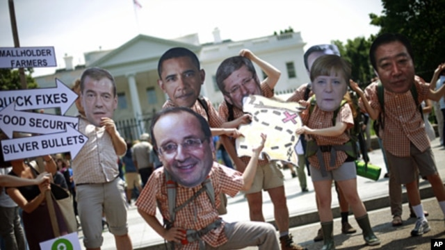 Activists wearing masks depicting G8 world leaders participate in a demonstration outside the White House in Washington, May 17, 2012. (AP)