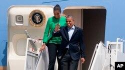 """Presiden Obama dan Ibu Negara Michelle Obama turun dari pesawat Kepresidenan AS """"Air Force One"""" setibanya di Bismarck, North Dakota dalam kunjungan ke Standing Rock Indian Reservation di Cannon Ball, North Dakota (13/6)."""