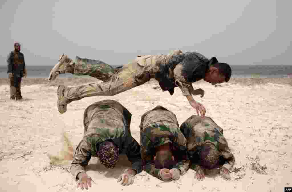 June 2: A Libyan volunteer jumps over his comrades during a military training course before going to the frontline in the rebelstrong hold of Benghazi, Libya. (AP Photo)