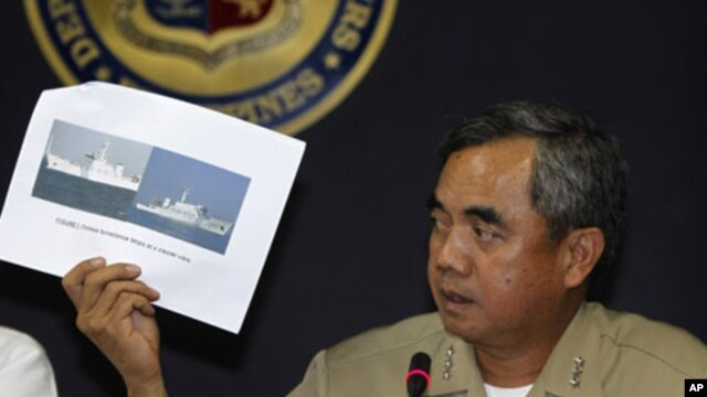Philippine Navy flag officer-in-command vice admiral Alexander Pama presents to the media an undated file photo of a Chinese surveillance ship which blocked a Philippine Navy ship from arresting Chinese fishermen, April 11, 2012.