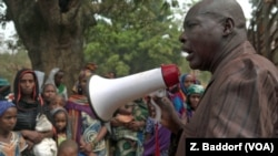 Ibrahim Abaka, the president of an internally displaced persons camp, uses a megaphone to organize the distribution of food aid in Bambari, Jan. 2017.