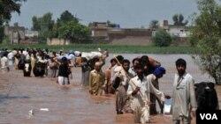 Para warga mengungsi sambil membawa sebagian barang mereka dari daerah Mohib Bhanda di distrik Nowshera.