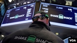 Specialist John O'Hara, wears Shake Shack promotional hat, sunglasses and vest as he works at his post on the floor of the New York Stock Exchange Friday, Jan. 30, 2015.