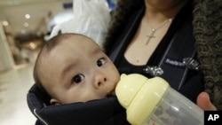 Miyako Ikeda feeds her baby Ryutaro drinking water after buying bottled water at a supermarket in Tokyo, March 25, 2011.