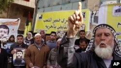 Warga Palestina memegang foto Khader Adnan, anggota senior Jihad Islam yang dipenjara di Israel sebagai dukungan atas aksi mogok makan warga Palestina dalam penjara (13/5). Para tahanan akhirnya menghentikan aksinya setelah mendapat kesepakatan dengan pem