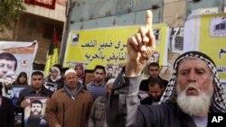 Warga Palestina memegang foto Khader Adnan, anggota senior Jihad Islam yang dipenjara di Israel sebagai dukungan atas aksi mogok makan warga Palestina dalam penjara pada 2012. (Foto: Dok)