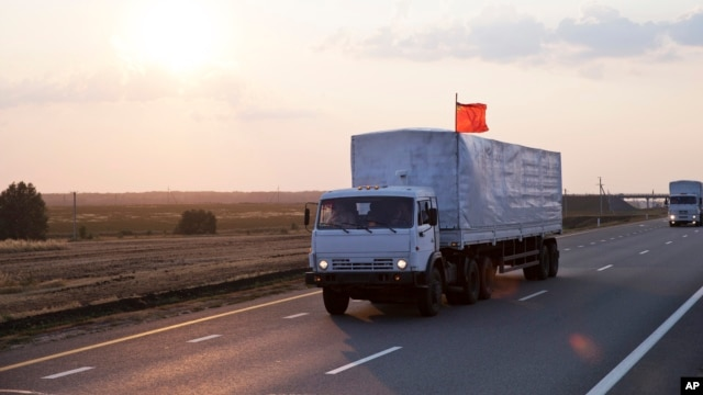 A convoy of white trucks carrying humanitarian aid passes along the main road M4 (Don highway) Voronezh region, Russia, Aug. 12, 2014