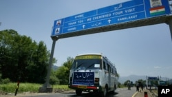 FILE - An Indian bus carrying passengers who arrived from the Pakistani side of Kashmir leaves the border at Chakka Da Bagh in Poonch district, 250 kilometers northwest of Jammu, India.