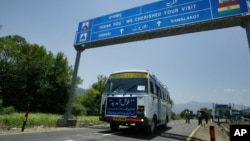 FILE - An Indian bus carrying passengers who arrived from the Pakistani side of Kashmir leaves the border at Chakka Da Bagh in Poonch district, 250 kilometers (156 miles) northwest of Jammu, India.