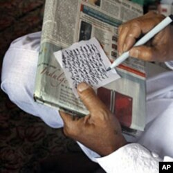 A June 19, 2011 photograph shows Mohammed Yousuf Roshangar, a Kashmiri Muslim faith healer, writing a taweez, a religious writing put inside amulets for protection and invoking blessing, in Srinagar, India