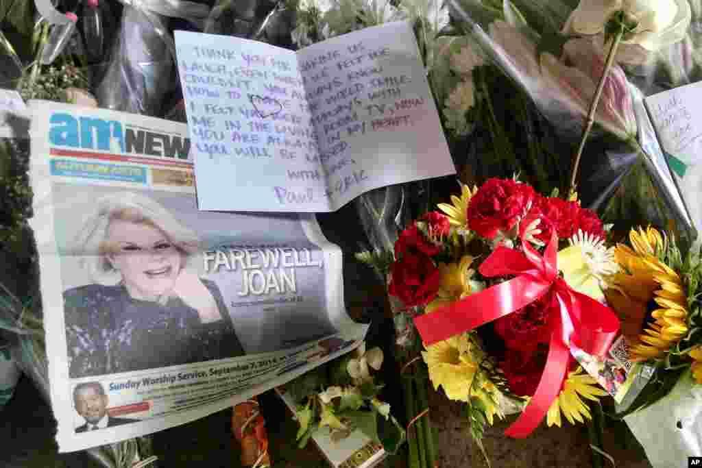 Một tờ báo, hoa và thiệp đặt trên vỉa hè trước ngưỡng cửa tòa nhà chung cư nơi nữ nghệ sĩ hài Joan Rivers sinh sống ở New York. Bà qua đời ở tuổi 81 hôm thứ Năm tại một bệnh viện ở New York vì biến chứng sau một cuộc phẫu thuật.