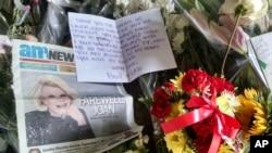 Karangan bunga, kartu tampak di pintu masuk gedung apartemen komedian Joan Rivers di New York (5/9).