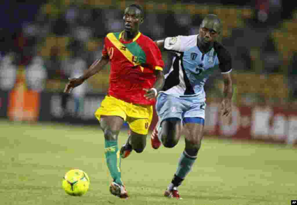 Guinea's Ismael Bangoura (L) challenges Botswana's Ndiyapo Letsholathebe for the ball during their African Nations Cup Group D soccer match at Franceville Stadium January 28, 2012.