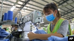 In this Oct. 24, 2017, photo, a garment worker sews clothes at Pro Sports factory in Nam Dinh province, Vietnam. (AP Photo/Hau Dinh)