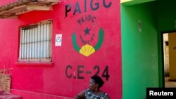 FILE - Dominga Lima, a member of the African Party for the Independence of Guinea and Cape Verde (PAIGC), sits in front of the party's logo at a campaign building in Bissau, Guinea-Bissau.