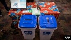 Une nouvelle machine à voter devant être utilisée lors des élections en République démocratique du Congo (RDC) est installée sur une table à côté de deux urnes le 21 février 2018 à Kinshasa.
