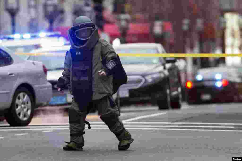 Một chuyên viên tháo gỡ bom mìn đi khỏi hiện trường sau khi chuẩn bị cho nổ có kiểm soát một vật nghi ngờ tại Watertown, Massachusetts, trong cuộc truy lùng nghi can vụ đánh bom Marathon Boston.