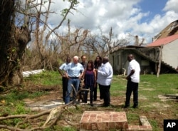 Vice President Mike Pence, joined by his wife Karen Pence, fourth from left, surveys hurricane damage outside Holy Cross Episcopal Church in St. Croix, U.S. Virgin Islands, Oct. 6, 2017.