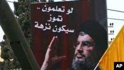 레바논 무장정파 헤즈볼라 전투원들이 지도자 나스랄라의 얼굴이 그려진 사진 밑에 서있다