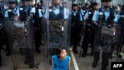 2019年6月12日,香港立法会外,一名抗议者坐在防暴警察面前。