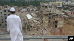 一名孟加拉國男子遙望工廠大樓坍塌的廢墟﹐救援人員繼續在現場進行救援工作。