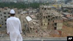 Čovek posmatra dok spasilačke ekipe tragaju za preživelima u srušenoj fabrici konfekcije u Savaru u blizini Dake, Bangladeš