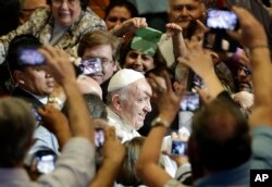Pope Francis is surrounded as he arrives for a meeting at the San Jose school stadium in Asuncion, Paraguay on July 11, 2015.