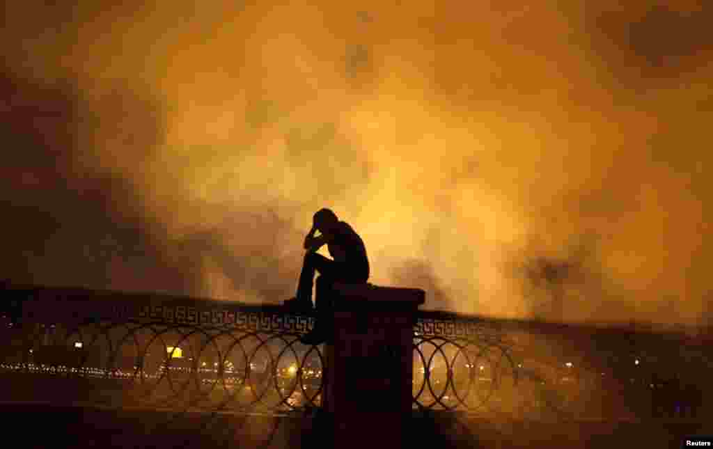 A protester covers his face in front of tear gas during clashes with riot police along a road at Kornish El Nile leading to the U.S. embassy, near Tahrir Square in Cairo, September 15, 2012.
