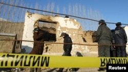 FILE - Security personnel inspect the site of a raid in the village of Besh-Kungei outside Bishkek, Kyrgyzstan, conducted as part of a military operation against suspected Islamist militants, Jan. 6, 2011.