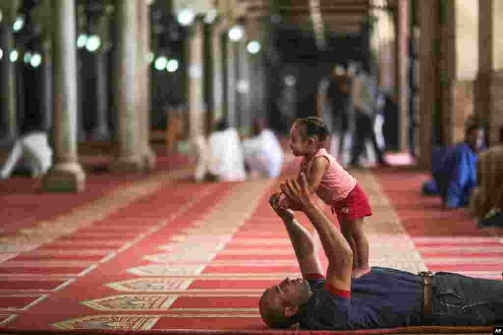Một người cha chơi với con gái sau buổi cầu nguyện chiều thứ Sáu tại Nhà thờ Hồi giáo Al-Azhar ở Cairo, Ai Cập.
