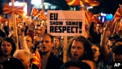 People protest in front of the Parliament building in Skopje, Macedonia, March 21, 2017. Tens of thousands of demonstrators gathered to protest a visit by a European Union envoy who is trying to break the political deadlock that has left the country without a government for three months.