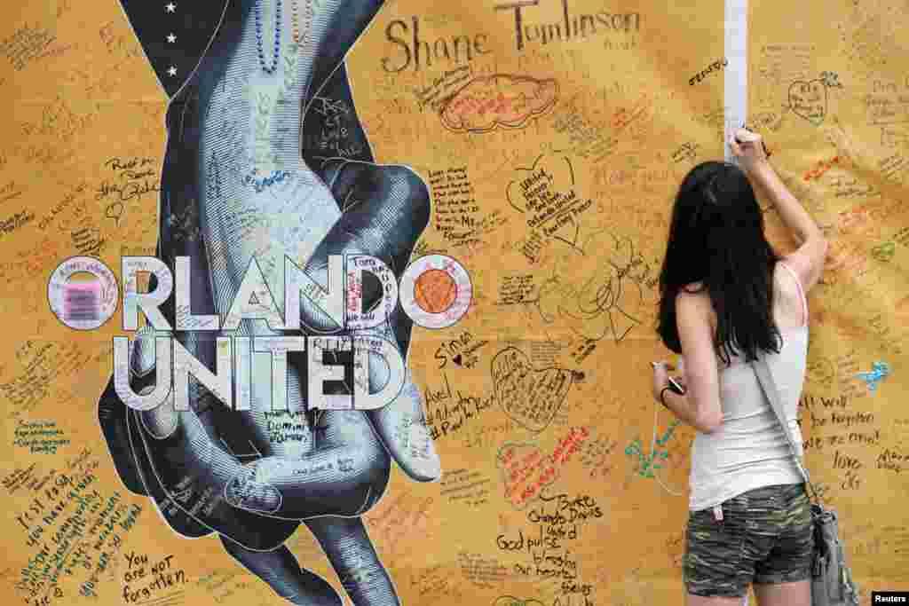 នាង Mary Beth Nickerson ចុះហត្ថលេខាលើជញ្ជាំងខាងក្រៅនៃក្លឹបកម្សាន្តពេលរាត្រី Pulse នៅពេលទៅគោរពវិញ្ញាណក្ខន្ធនៃខួបមួយឆ្នាំនៃការបាញ់ប្រហារនៅក្នុងក្រុង Orlando រដ្ឋ Florida សហរដ្ឋអាមេរិក។