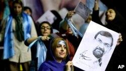 Seorang pendukung kandidat presiden Mohsen Rezaei, mantan komdandan Tentara Revolusi Iran, memegang poster capresnya di saat kampanye di Teheran, Iran (10/6). Pemilu Iran akan diselenggarakan hari Jumat, 14 Juni 2013 mendatang.