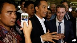 인도네시아를 방문한 페이스북 CEO 마크 저커버그(오른쪽)가 조코 위도도 대통령 당선자(가운데)와 자카르타의 시장을 둘러보고 있다.