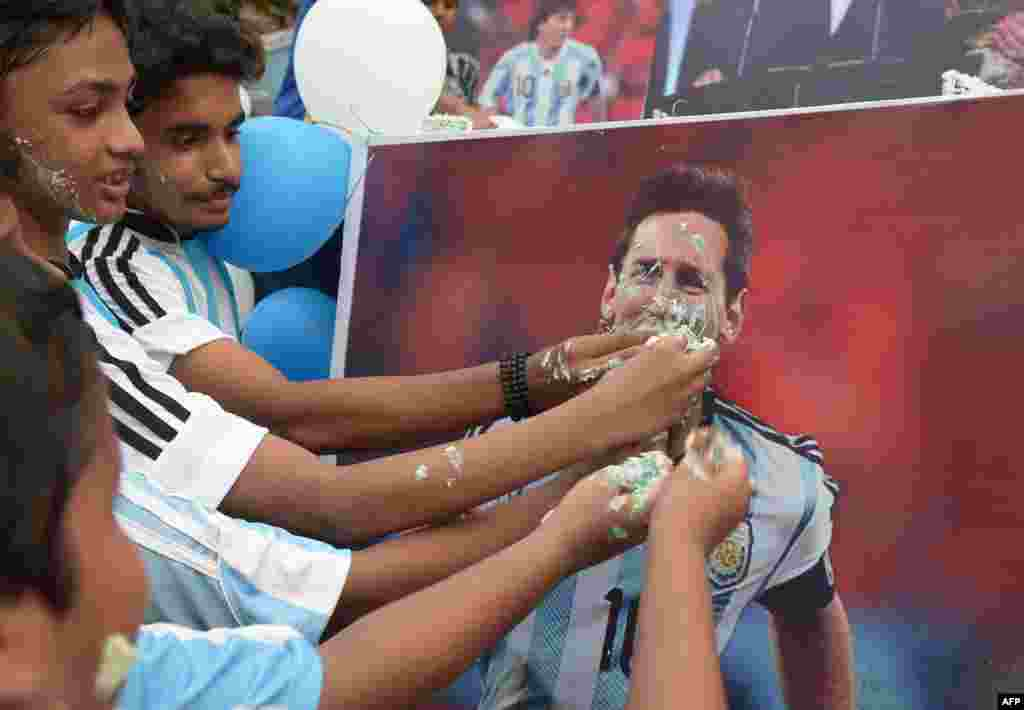 Indian football fans pose for photographers as they feed cake to a poster of Argentine striker Lionel Messi during an event to mark his birthday in Kolkata, ahead of the Copa America final where Argentina will take on Chile.