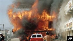 A Korean-American shopping mall burns at Third Street and Vermont Avenue in Los Angeles on April 30, 1992, the second day of rioting in the city over a police beating case