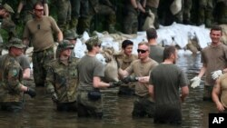 German Bundeswehr soldiers and other helpers pile sandbags in Rothensee, a suburb of Magdeburg, at river Elbe, eastern Germany, June 9, 2013.